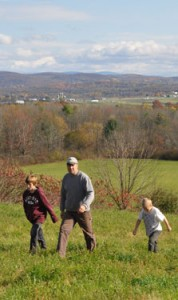 New York farmer walking through field with sons