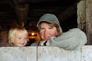Woman farmer and child looking out of a barn